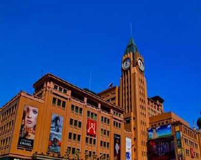 """中华人民共和国成立后北京建造的第一座大型百货零售商店,被誉为""""新中国第一店""""。位于王府井大街。以经营日用百货为主(1997年底经营品种达498万种)。1955年9月开业,名为北京市百货公司王府井百货商店。1968年7月改为现名。 建筑面积3.9万平方米,营业面积1.8万平方米。1970年扩建附属业务楼和仓库楼。1989年增建玩具娱乐品商场,晋升为国家二级企业。1991年成立北京百货大楼集团。1993年进行股份制改造。1994年北京王府井百货(集团)股份有限公司在上海证券交易所上市。1999年新建北部商业楼。2000年王府井百货和东安集团公司实现资产重组,成立北京王府井东安集团有限责任公司。2004年2月百货大楼开始进行内部升级改造,4月对外营业。百货大楼售货员张秉贵是全国著名劳动模范,大楼前广场立有其半身铜像,陈云在基石上题词""""一团火精神光跃神州""""。"""